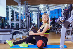 Beautiful blonde girl in sportswear on the floor with  ball gym Stock Images