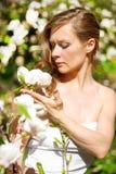 Beautiful blonde girl in spring garden. Beautiful blonde girl with magnolia in spring garden Stock Image