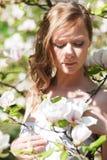 Beautiful blonde girl in spring garden. Beautiful blonde girl with magnolia in spring garden Royalty Free Stock Images
