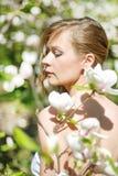 Beautiful blonde girl in spring garden. Beautiful blonde girl with magnolia in spring garden Royalty Free Stock Photo