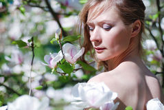 Beautiful blonde girl in spring garden. Beautiful blonde girl with magnolia in spring garden Royalty Free Stock Photography