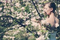 Beautiful blonde girl in spring garden. Beautiful blonde girl with magnolia in spring garden Stock Photo