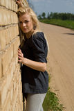 Beautiful blonde girl is standing against the wall Stock Photography