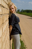Beautiful blonde girl is standing against the wall Stock Photo