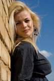 Beautiful blonde girl is standing against the wall Royalty Free Stock Image