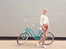 Beautiful blonde girl is standing near the vintage bicycle with brown vintage bag have fun and good mood looking in camera and smi Royalty Free Stock Images