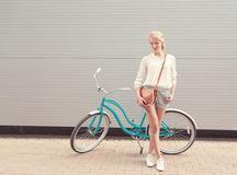 Beautiful blonde girl is standing near the vintage bicycle with brown vintage bag have fun and good mood looking in camera and smi Royalty Free Stock Photo