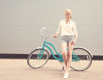 Beautiful blonde girl is standing near the vintage bicycle have fun and good mood looking in camera and smiling, warm, tonning Royalty Free Stock Photography
