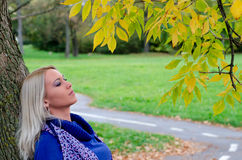 Beautiful blonde girl standing in the park on autumn day Stock Photo