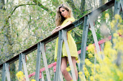 Beautiful blonde girl standing in a rural bridge. Beautiful blonde girl, dressed with a green dress, standing in a rural bridge royalty free stock photo