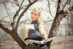 Beautiful blonde girl standing under a tree. With an album in the hands of Stock Image