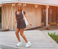 Beautiful blonde girl in summer short dress and white fashionable sneakers dancing, having fan. Outdoor Royalty Free Stock Photography