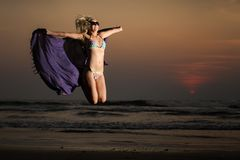 Beautiful blonde girl. In swimming suit jump with purple scarf on beach on sunset royalty free stock photos