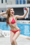 Beautiful blonde girl in swimsuit doing selfie. Beautiful young blonde girl in swimsuit doing selfie Royalty Free Stock Image