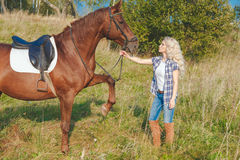 Beautiful blonde girl taking care of the horse at the ranch.  Stock Photo