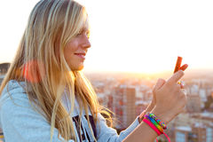 Beautiful blonde girl taking pictures of the city. Royalty Free Stock Photo