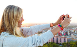 Beautiful blonde girl taking pictures of the city. Royalty Free Stock Image