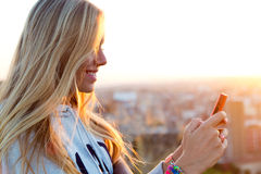 Beautiful blonde girl taking pictures of the city. Royalty Free Stock Photos