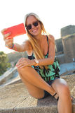 Beautiful blonde girl taking a selfie on the roof. Royalty Free Stock Photos