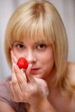 Beautiful blonde girl tempts us fresh strawbery Stock Image