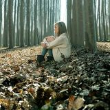 Beautiful blonde girl thinking in the woods Stock Photos