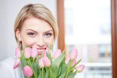Beautiful blonde girl with tulips Stock Images