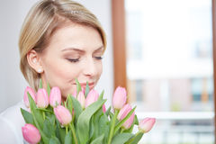 Beautiful blonde girl with tulips Stock Photography