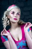 Beautiful blonde girl with two pigtails, with creative doll make-up: pink glossy lips, wearing pink skeleton dress. for the Hallow Stock Photos