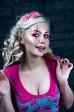 Beautiful blonde girl with two pigtails, with creative doll make-up: pink glossy lips, wearing pink skeleton dress. for the Hallow. Beautiful blonde girl with Royalty Free Stock Photo