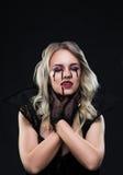Beautiful blonde girl vampire is strangling herself Royalty Free Stock Photo