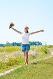 Beautiful blonde girl walking barefoot on summer field with a bouquet of wild flowers Royalty Free Stock Images