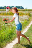 Beautiful blonde girl walking barefoot on summer field with a bouquet of wild flowers Royalty Free Stock Photo