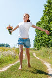 Beautiful blonde girl walking barefoot on summer field with a bouquet of wild flowers. Pretty young woman with a bouquet of wild flowers outdoors. Beautiful Stock Photos