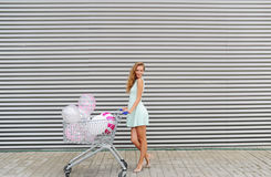 Beautiful blonde girl with waving hair running and rolling shopping cart with color balloons. Stock Image