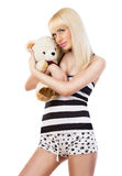 Beautiful blonde girl wearing pajamas embraces teddy bear Stock Image