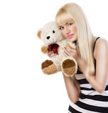 Beautiful blonde girl wearing pajamas embraces teddy bear Stock Photography