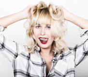 Beautiful blonde girl wearing a plaid shirt showing tongue and clutched his hands in her hair stock images
