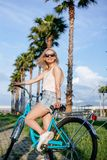 Joyful blonde woman riding bicycle in park having fun on summer afternoon stock photos