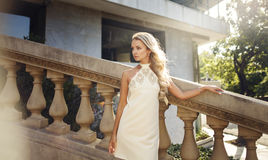 Beautiful blonde girl in white dress on the stairs Stock Photos