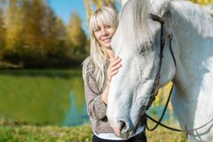 Beautiful blonde girl with a white horse posing in the autumn forest. Horizontal portrait royalty free stock photo