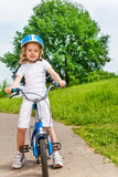 Beautiful blonde girl in white sitting on bicycle Stock Photos