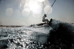 Blonde girl riding on the wakeboard holding a rope royalty free stock image
