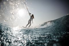 Blonde girl standing on the wakeboard holding a rope. Beautiful blonde girl in the white swimsuit standing on the wakeboard holding a rope on the bending knees royalty free stock images