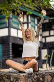 Beautiful blonde girl in white t-shirt doing yoga. Women`s hands with a tattoos. Urban fashion. Beautiful blonde girl in white t-shirt doing yoga. Women`s hands royalty free stock photo