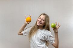 Beautiful blonde girl in a white T-shirt smiles and holds an apple and an orange in her hands. Healthy nutrition for stock image