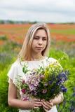 Beautiful blonde girl with wildflowers Stock Image