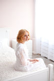 Beautiful blonde girl woke up and sitting on a bed Royalty Free Stock Image