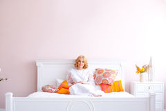 Beautiful blonde girl woke up and sitting on a bed Stock Photo