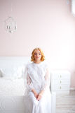 Beautiful blonde girl woke up and sitting on a bed Royalty Free Stock Photo