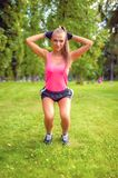 Beautiful blonde girl working out in park doing squats Royalty Free Stock Photos